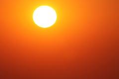 Πορτοκαλής ουρανός γύρω από το λευκό του ήλιου Στοκ Εικόνες