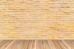 Πορτοκαλής τουβλότοιχος ως ωραία κατασκευασμένο υπόβαθρο στο ξύλινο πάτωμα Στοκ Φωτογραφία