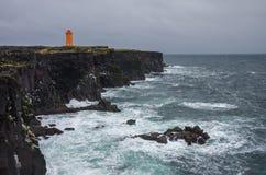 Πορτοκαλής φάρος στο μαύρο απότομο βράχο βράχου των δυτικών ισλανδικών Στοκ Φωτογραφία