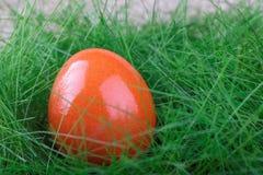 Πορτοκαλί αυγό Πάσχας στην πράσινη χλόη Στοκ Φωτογραφία