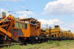 Πορτοκαλί αυτοκίνητο υπηρεσιών διαδρομής σιδηροδρόμων Η συντριμμένη πέτρα εγκαθιστά το κατασκεύασμα Στοκ Φωτογραφία