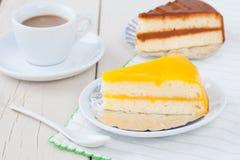 Πορτοκαλί κέικ στο άσπρο πιάτο στον ξύλινο πίνακα με τον καφέ και coffe Στοκ Φωτογραφία