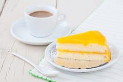 Πορτοκαλί κέικ στο άσπρο πιάτο στον ξύλινο πίνακα με τον καφέ Στοκ φωτογραφία με δικαίωμα ελεύθερης χρήσης