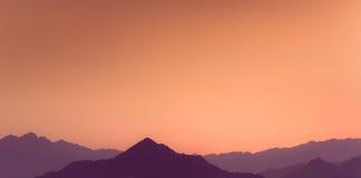 Πορτοκαλί και κίτρινο ηλιοβασίλεμα επάνω από τα στρώματα των βουνών Στοκ Φωτογραφία