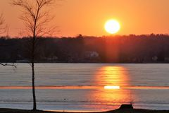 Πορτοκαλί και κίτρινο ηλιοβασίλεμα πέρα από την παγωμένη λίμνη Στοκ Φωτογραφία