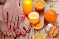 Πορτοκαλί μανικιούρ γύρω από τα πορτοκάλια και τα κεριά Στοκ Εικόνες