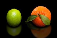 Πορτοκαλί μανταρίνι και πράσινος ασβέστης στο καθαρό μαύρο υπόβαθρο Στοκ φωτογραφίες με δικαίωμα ελεύθερης χρήσης