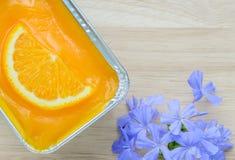 Πορτοκαλί μαλακό κέικ με το μπλε λουλούδι Στοκ Φωτογραφίες