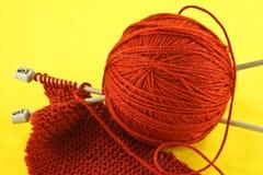 Πορτοκαλί νήμα και πλέκοντας βελόνες Στοκ Φωτογραφία