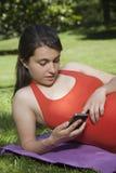 Πορτοκαλί πουκάμισο έγκυο με το smartphone Στοκ Φωτογραφία