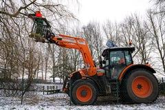 Πορτοκαλί τρακτέρ με τον υδραυλικό ανελκυστήρα και ένας υλοτόμος με το chainsa Στοκ φωτογραφίες με δικαίωμα ελεύθερης χρήσης