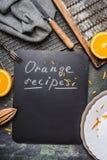Πορτοκαλί υπόβαθρο συνταγών με τα εργαλεία κουζινών, τον πίνακα κιμωλίας και τα πορτοκαλιά φρούτα, τοπ άποψη Στοκ εικόνα με δικαίωμα ελεύθερης χρήσης