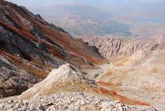Πορτοκαλί φαράγγι στο υπόβαθρο του πανοράματος των βουνών της Τιέν Σαν στοκ φωτογραφία
