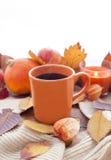 Πορτοκαλί φλυτζάνι καφέ στα φύλλα πτώσης φθινοπώρου Στοκ εικόνα με δικαίωμα ελεύθερης χρήσης