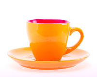 Πορτοκαλί φλυτζάνι χρώματος στο πιάτο Στοκ Φωτογραφία
