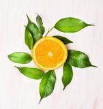 Πορτοκαλί lobule με τα πράσινα φύλλα στον άσπρο ξύλινο πίνακα Στοκ εικόνες με δικαίωμα ελεύθερης χρήσης
