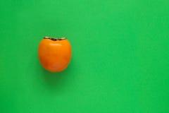 Πορτοκαλί persimmon σε πράσινο Στοκ Εικόνα