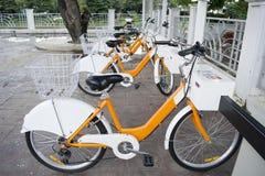 Πορτοκαλιά άσπρα δημόσια ποδήλατα για το μίσθωμα στην αγορά Waroros, Chiang Mai Ταϊλάνδη Στοκ Εικόνες