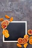 Πορτοκαλιά δαχτυλίδια σε έναν μαύρο πίνακα κιμωλίας Στοκ Εικόνες