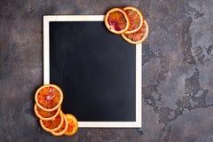 Πορτοκαλιά δαχτυλίδια σε έναν μαύρο πίνακα κιμωλίας Στοκ φωτογραφία με δικαίωμα ελεύθερης χρήσης