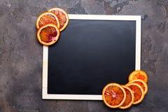 Πορτοκαλιά δαχτυλίδια σε έναν μαύρο πίνακα κιμωλίας Στοκ φωτογραφίες με δικαίωμα ελεύθερης χρήσης