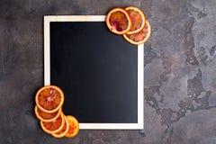 Πορτοκαλιά δαχτυλίδια σε έναν μαύρο πίνακα κιμωλίας Στοκ Εικόνα