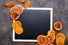 Πορτοκαλιά δαχτυλίδια σε έναν μαύρο πίνακα κιμωλίας Στοκ εικόνα με δικαίωμα ελεύθερης χρήσης