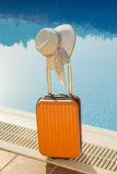 Πορτοκαλιά βαλίτσα και ένα καπέλο στο poolside Στοκ Εικόνα