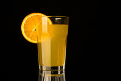 Πορτοκαλιά λεμονάδα με το κομμάτι του πορτοκαλιού στο γυαλί στο μαύρο υπόβαθρο Στοκ Εικόνα