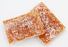 Πορτοκαλιά ζελατίνα φρούτων με την καρύδα σε ένα γκρίζο υπόβαθρο Στοκ Εικόνες