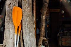 Πορτοκαλιά κουπιά σε ένα ξύλινο υπόβαθρο Δύο πορτοκαλιά κουπιά για μια βάρκα ή ένα καγιάκ θάλασσας στοκ εικόνα
