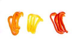 Πορτοκαλιά, κόκκινα και κίτρινα πιπέρια λουρίδων στο άσπρο υπόβαθρο Στοκ Εικόνες