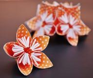 Πορτοκαλιά λουλούδια origami φιαγμένα από διαστιγμένο Πόλκα έγγραφο Στοκ Φωτογραφίες