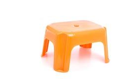 Πορτοκαλιά παραδοσιακή μίνι πλαστική καρέκλα τεσσάρων ποδιών στο μόριο Στοκ εικόνες με δικαίωμα ελεύθερης χρήσης