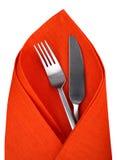 Πορτοκαλιά πετσέτα με το μαχαίρι και δίκρανο που απομονώνεται Στοκ Φωτογραφία