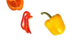 Πορτοκαλιά πιπέρια, κόκκινα και κίτρινα μισά και λουρίδων στο άσπρο υπόβαθρο Στοκ εικόνα με δικαίωμα ελεύθερης χρήσης
