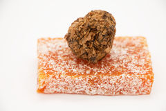Πορτοκαλιά τουρκική απόλαυση με την καραμέλα σοκολάτας σε ένα γκρίζο υπόβαθρο Στοκ Εικόνα