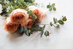 Πορτοκαλιά τριαντάφυλλα και διακοσμητικοί κλάδοι στο άσπρο κατασκευασμένο backgroun Στοκ Εικόνα