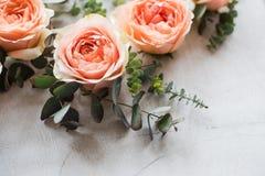 Πορτοκαλιά τριαντάφυλλα και διακοσμητικοί κλάδοι στο άσπρο κατασκευασμένο backgroun Στοκ Εικόνες