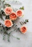 Πορτοκαλιά τριαντάφυλλα και διακοσμητικοί κλάδοι στο άσπρο κατασκευασμένο backgroun Στοκ φωτογραφία με δικαίωμα ελεύθερης χρήσης