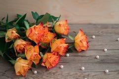 Πορτοκαλιά τριαντάφυλλα σε ένα ξύλινο υπόβαθρο και διεσπαρμένες χάντρες των μαργαριταριών Στοκ Φωτογραφία