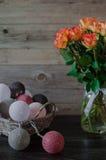 πορτοκαλιά τριαντάφυλλ&alph Ψάθινο καλάθι με τη γιρλάντα υπό μορφή σφαιρών, που τυλίγονται στο χρωματισμένο νήμα Στοκ εικόνα με δικαίωμα ελεύθερης χρήσης