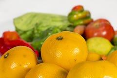 Πορτοκαλιά tangerines μπροστά από διάφορα φρούτα και λαχανικά Στοκ φωτογραφία με δικαίωμα ελεύθερης χρήσης