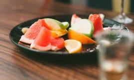 Πορτοκαλιές φέτες, φέτες της Apple, τμήματα γκρέιπφρουτ στο μαύρο πιάτο Στοκ Εικόνες