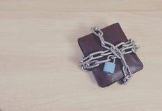 Πορτοφόλι κλειστό στο αλυσίδες λουκέτο στο ξύλινο πάτωμα στοκ εικόνα με δικαίωμα ελεύθερης χρήσης