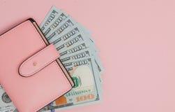 Πορτοφόλι με τα τραπεζογραμμάτια εκατό δολαρίων στο ρόδινο υπόβαθρο Επίπεδος βάλτε, τοπ άποψη, διάστημα αντιγράφων στοκ φωτογραφία