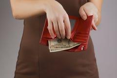 Πορτοφόλι με τα χρήματα στα χέρια των γυναικών, κατανάλωση χρημάτων Στοκ Εικόνα