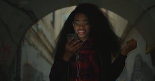 Πορτρέτου ευτυχής όμορφος ελκυστικός αφρικανικός κοριτσιών χαμόγελου χορός ακουστικών μουσικής ακούσματος εκμετάλλευσης κινητός 4 απόθεμα βίντεο
