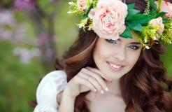 Πορτρέτο άνοιξη μιας όμορφης γυναίκας σε ένα στεφάνι των λουλουδιών στοκ φωτογραφία