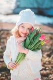 Πορτρέτο άνοιξη του ευτυχούς κοριτσιού παιδιών με την ανθοδέσμη τουλιπών για την ημέρα της γυναίκας Στοκ Εικόνες